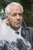 Serious businessman on the phone driving
