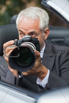Mature paparazzi taking picture with his professional camera