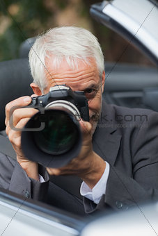 Mature paparazzi taking picture with professional camera