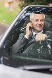 Smiling businessman on the phone driving expensive cabriolet