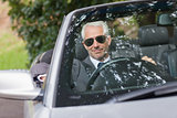 Cheerful mature businessman driving classy cabriolet