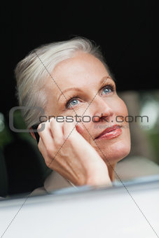 Businesswoman on the phone driving classy car