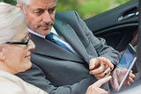 Partners working together on tablet in classy convertible