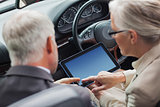 Mature partners working together on tablet in classy convertible
