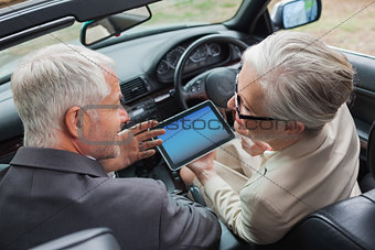 Smiling mature partners working together on tablet in classy car