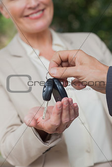 Close up on smiling businesswoman being given keys
