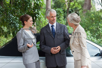 Smiling business people talking together by classy cabriolet