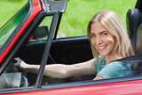 Cheerful woman driving red cabriolet