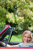 Happy blonde woman driving red cabriolet