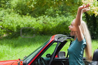 Cheerful blonde enjoying her red cabriolet