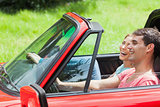 Smiling young couple having a ride in red cabriolet