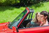 Pretty blonde kissing her boyfriend in red cabriolet