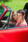 Happy blonde kissing her boyfriend in red cabriolet