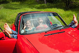Cheerful young couple relaxing in classy cabriolet