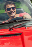 Cheerful handsome man driving his cabriolet