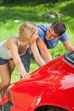 Happy couple pushing their broken down car