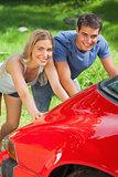 Smiling couple pushing their broken down car