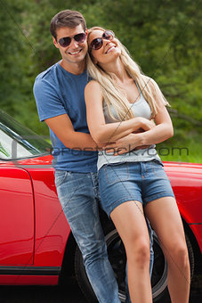 Loving couple hugging and leaning against cabriolet