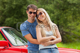 Cheerful couple hugging and leaning against cabriolet