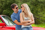 Cheerful young couple hugging and leaning against cabriolet