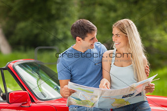 Happy young couple reading map