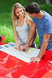 Smiling young couple reading map on their cabriolet bonnet