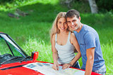 Happy young couple reading map on their cabriolet bonnet