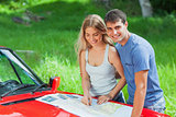 Cheerful young couple reading map on their cabriolet bonnet