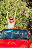 Loving couple having fun in their red convertible