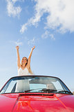 Cheerful woman standing in cabriolet while her boyfriend driving