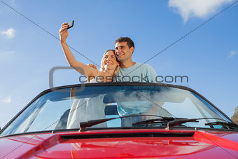 Cheerful couple standing in red cabriolet taking picture