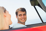 Smiling man looking at his pretty girlfriend while driving
