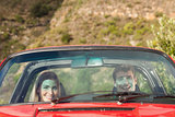Front view of smiling couple in red cabriolet