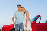Smiling cute couple posing against their red cabriolet