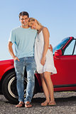 Happy cute couple posing against their red cabriolet