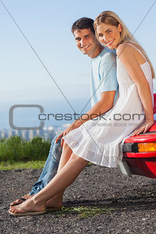 Happy couple sitting on their cabriolet car hood