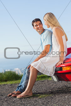Smiling couple sitting on their cabriolet car hood