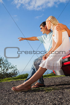 Cheerful cute couple sitting on their cabriolet car hood