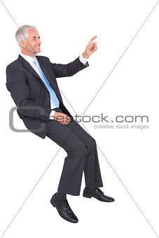 Smiling businessman sitting and pointing finger