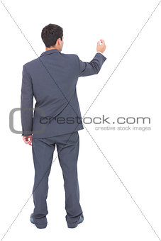 Businessman standing back to camera writing with marker