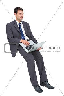 Smiling businessman sitting using a laptop