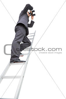 Low angle view of businessman standing on ladder using binoculars