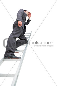 Low angle view of businessman standing on ladder