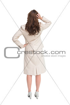 Businesswoman standing back to camera with hand on head