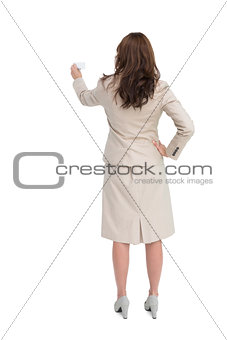 Businesswoman holding business card standing back to camera