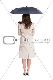 Rear view of classy businesswoman holding umbrella
