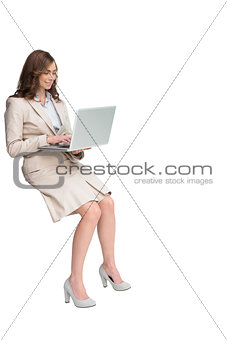 Smiling businesswoman sitting and using laptop
