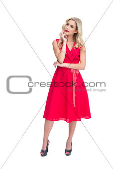 Thoughtful woman posing in red dress