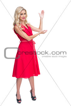 Woman wearing red dress presenting something