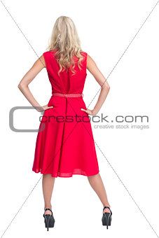 Rear view of gorgeous blonde in red dress posing